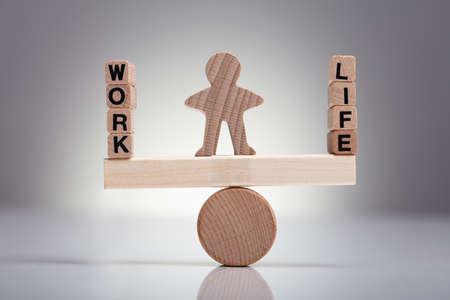 Human Figure Balancing Between Work And Life On Wooden Seesaw Against Gray Background Standard-Bild