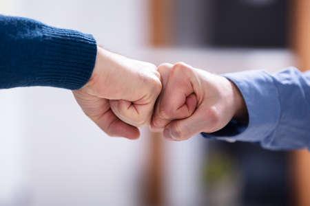 Nahaufnahme von zwei Geschäftsleuten, die Fauststoß im Amt machen Standard-Bild