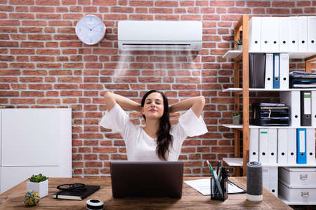 Relaxed Businesswoman Enjoying The Cooling Of Air Conditioner In The Office Zdjęcie Seryjne