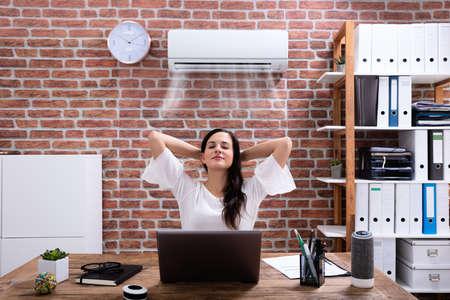 Zrelaksowana bizneswoman ciesząca się chłodzeniem klimatyzatora w biurze
