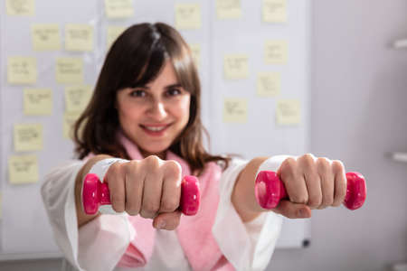 Smiling Young Businesswoman Exercising With Red Dumbbells In Office Stock Photo