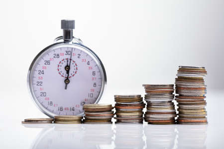 Close-up Of Stopwatch With Increasing Stacked Coins On Reflective Desk Imagens