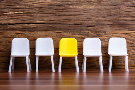 Miniature Chair In A Row With A Yellow One In The Middle On Wooden Background
