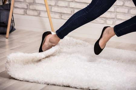 여자의 낮은 섹션이 카펫에 걸려 넘어진다.