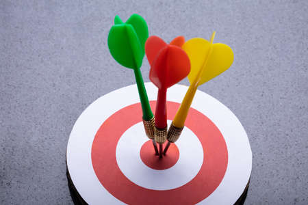 An Elevated View Of Colorful Darts On Target Against Gray Background 写真素材