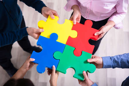 An Elevated View Of Hands Holding Colorful Jigsaw Puzzle