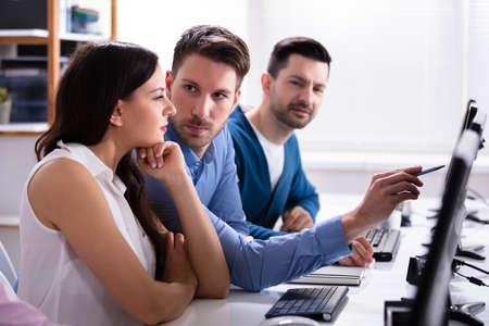 Uomo d'affari che punta sullo schermo del computer mentre parla con il suo collega