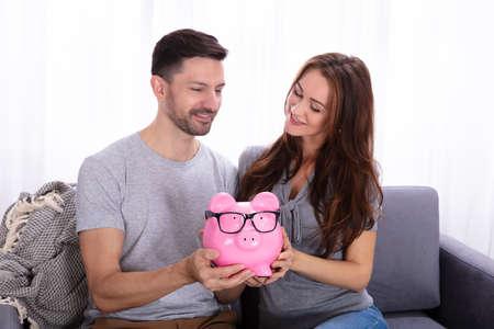 Sonriente pareja joven sentada en un sofá sosteniendo alcancía rosa