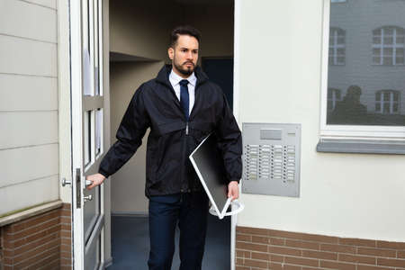 Young Male Technician Opening Door While Carrying Desktop In Hand Stock fotó