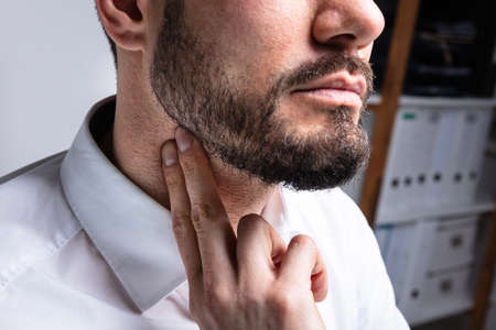 Close-up Of Young Man Touching His Neck To Eliminate High Blood Pressure Stock Photo