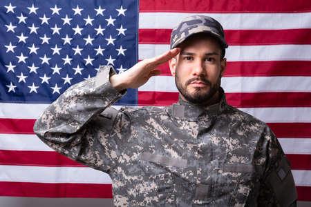 Porträt eines männlichen Soldaten, der gegen die amerikanische Flagge salutiert