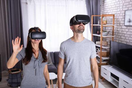 Jeune couple assis sur un canapé faisant l'expérience d'un casque de réalité virtuelle