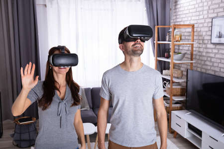 Young Couple Sitting On Sofa Experiencing Virtual Reality Headset