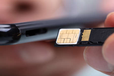 Close-up Of Person Inserting Sim Card And Memory Card In Mobile Phone