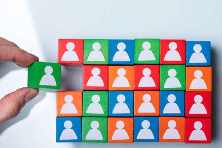 Businesspersons Hand Holding Green Cubic Block Near Team Of Red And Green Blocks Reklamní fotografie