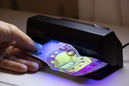 Nahaufnahme der Hand des Mannes, die Banknote durch Währungsdetektor-Technologie auf weißem Schreibtisch überprüft