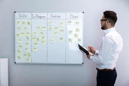 Zijaanzicht van zakenman schrijven op plaknotities gekoppeld aan White Board In Office