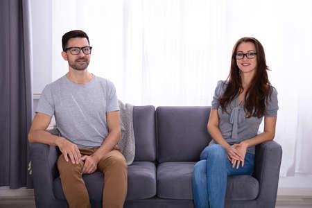 Giovani coppie che si siedono sul sofà che si guardano