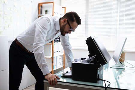 Young Irritated Businessman Looking At Printer In Office