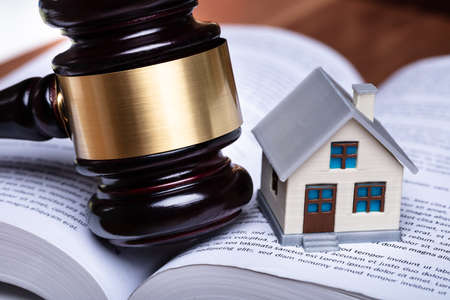 Close-up Of Miniature House And Gavel On Open Book Banque d'images