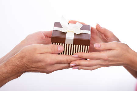Close-up Of Couple's Hand Holding Gift Box Against White Background