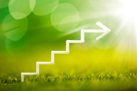 Close-up Of White Increasing Staircase Arrow On Grass Stock fotó