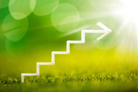 Nahaufnahme des weißen zunehmenden Treppenhauspfeils auf Gras Standard-Bild