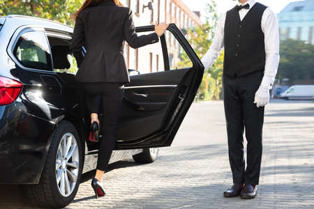 Male Valet Opening Door For Businesswoman Getting Out Of A Car On Street Stock Photo