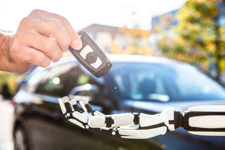 Close-up Of A Man's Hand Giving Car Key To Robot