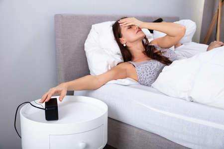 Jonge vrouw die op bed slaapt en de wekker in de slaapkamer uitzet Stockfoto