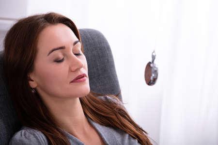 Jolie jeune femme hypnotisée avec pendule à la maison Banque d'images