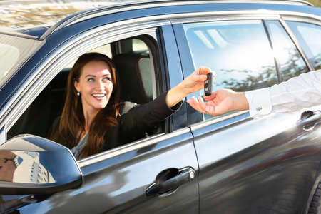 Smiling Young Woman Sitting In Car And Giving Car Key To Male Hand