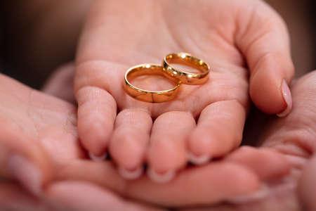 Mano di uomo e donna con coppia di anelli di fidanzamento dorati