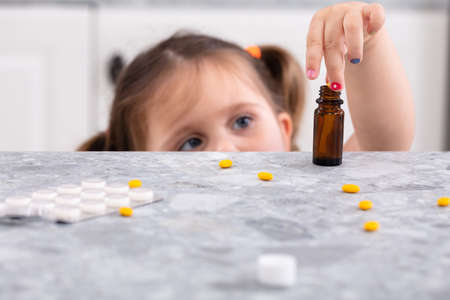 Cute Little Girl Trying To Take Pills On Marble Worktop