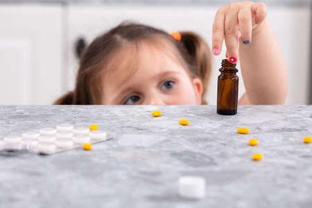 Nettes kleines Mädchen, das versucht, Pillen auf Marmorarbeitsplatte zu nehmen