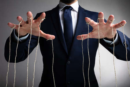 Man's Hand Controls The Puppet With The Fingers Attached To Threads Against Gray Background Banco de Imagens