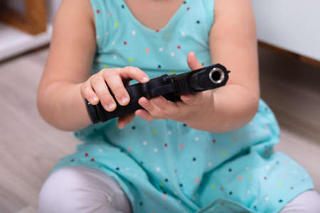 Close-up Of Little Girl's Hand Holding Gun At Home