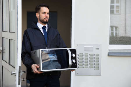 Male Technician Holding Microwave Standing Near Intercom