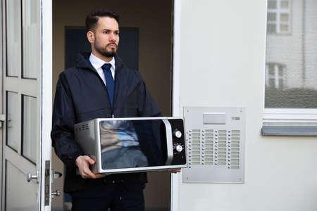 Technicien masculin tenant un micro-ondes debout près de l'interphone