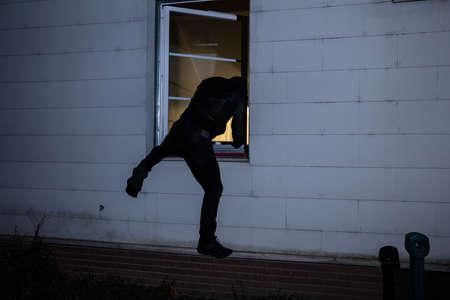 Rear View Of A Burglar Entering In A House Through A Window Stock Photo