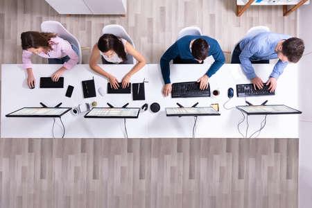 Jóvenes empresarios analizando el diagrama de Gantt en la computadora en el lugar de trabajo