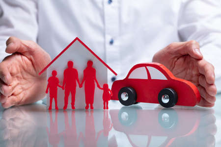 Photo Of Businessman Protecting Family Figure, House Model And Car 写真素材