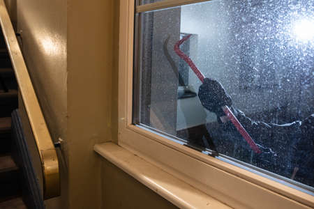 Burglar Trying To Open Window With Crowbar At Night Stock Photo