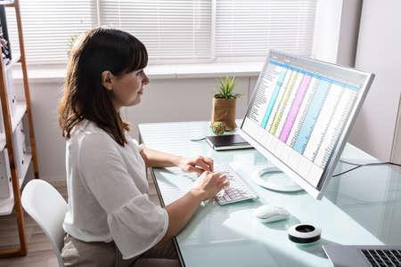 Zijaanzicht van de hand van de zakenvrouw die gegevens op de computer over het bureau analyseert