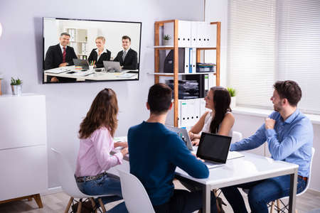 Rear View Of Businesspeople Attending Videoconference Meeting In Office Imagens