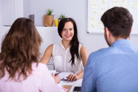 Businessman And Businesswoman Taking Interview Of Young Smiling Woman Stockfoto