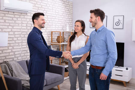 Smiling Male Real Estate Agent Shaking Hands With His Clients In New Home