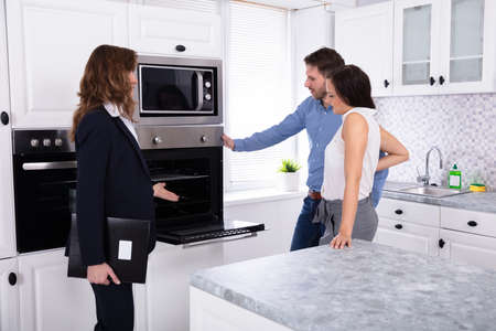 Real Estate Agent Showing Microwave Oven In House To A Young Couple