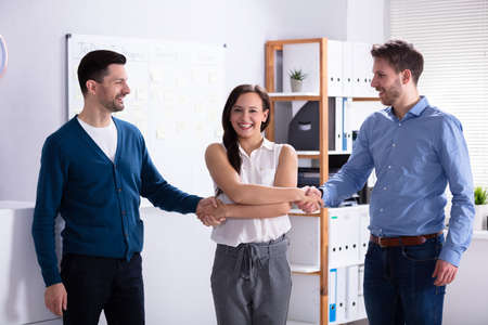 Woman Acting As Middleman In Deal Shaking Hands Imagens