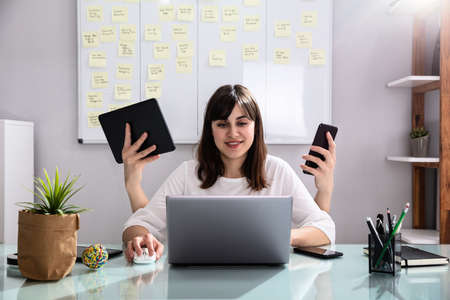 Smiling Young Businesswoman Doing Multitasking Work At Workplace